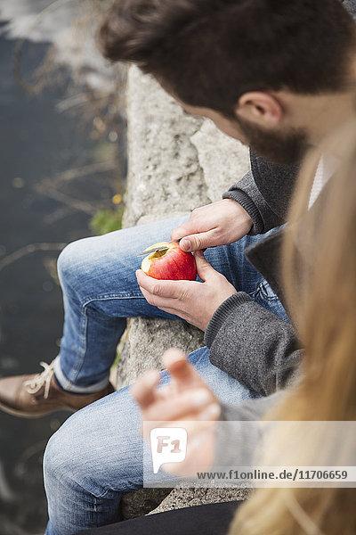 Paar auf Wand sitzend  Apfel schälend Paar auf Wand sitzend, Apfel schälend