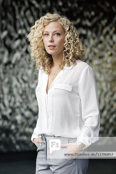 Porträt einer blonden Geschäftsfrau mit Händen in den Taschen