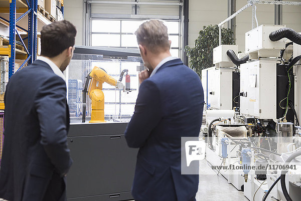 Zwei Geschäftsleute in der Fabrikhalle mit Blick auf Industrieroboter