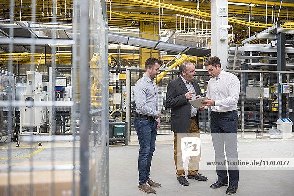 Drei Männer mit Tabletten reden in der Fabrikhalle