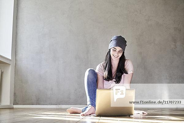 Lächelnde junge Frau auf dem Boden sitzend mit Laptop