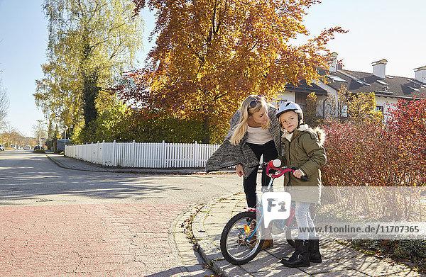 Mutter im Gespräch mit Tochter mit Fahrrad