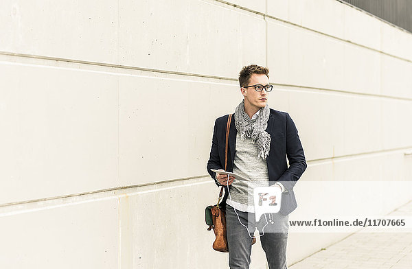 Young businessman walking in the street  carrying digital tablet and ear phones