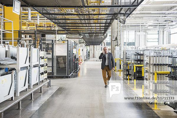 Businessman walking in factory shop floor talking on the phone