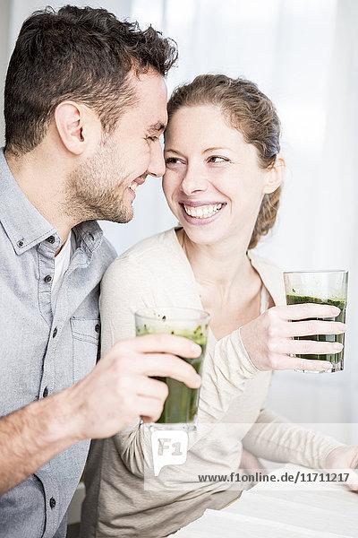 Ein glückliches Paar  das zusammen Smoothie trinkt.