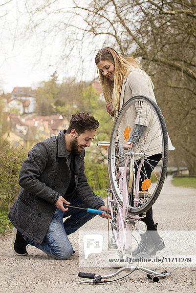 Junger Mann beim Aufpumpen von Fahrradreifen für seine Freundin