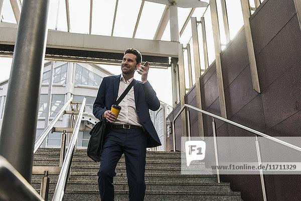 Ein Geschäftsmann am Telefon  der die Treppe runtergeht.