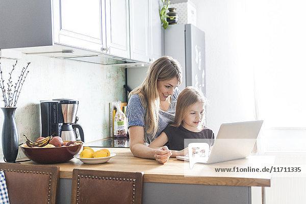 Mutter und Tochter mit Laptop in der Küche