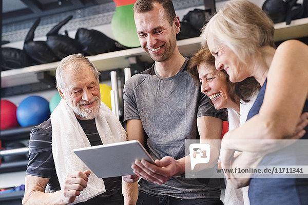 Gruppe von fit Senioren und Personal Trainer im Fitnessstudio mit Blick auf Tablette