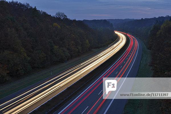 Deutschland  Bayern  Ampelpfade auf der Autobahn bei Dämmerung