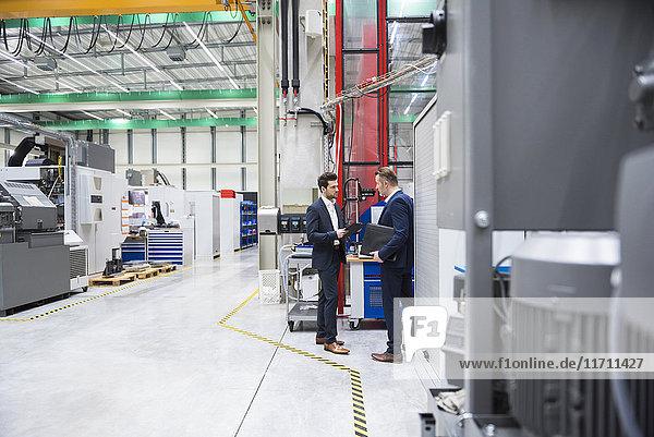 Zwei Geschäftsleute in der Fabrikhalle
