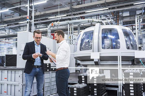 Zwei Männer in der Fabrik  die das Produkt untersuchen.