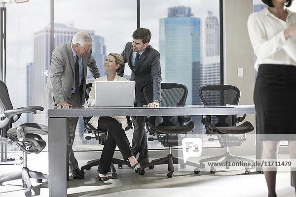 Gruppe von Geschäftsleuten mit Laptop diskutieren im Büro