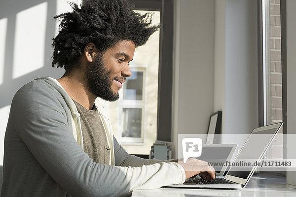 Mann arbeitet vor dem Fenster zu Hause mit Laptop