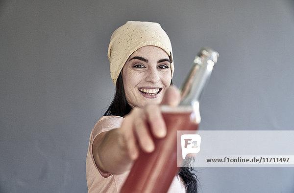 Porträt einer lächelnden jungen Frau mit Flasche