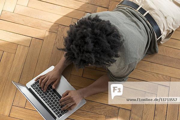 Auf dem Boden liegender Mann bei der Arbeit am Laptop