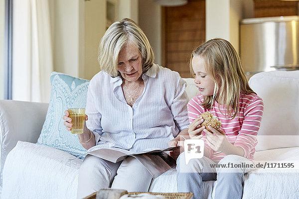 Großmutter und Enkelin sitzen nebeneinander auf der Couch und schauen sich ein Buch an.