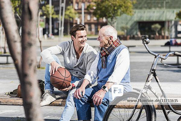 Senior Mann und erwachsener Enkel mit Basketball auf einer Bank im Gespräch