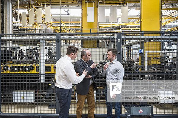 Drei Männer  die in der Fabrikhalle reden.