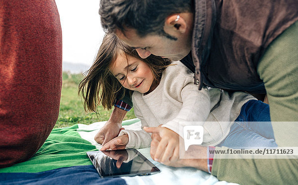 Glückliches Mädchen und ihr Vater benutzen Tabletten  die auf einer Decke im Freien liegen