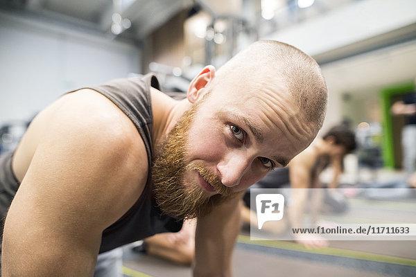 Porträt eines jungen Mannes  der im Fitnessstudio trainiert.