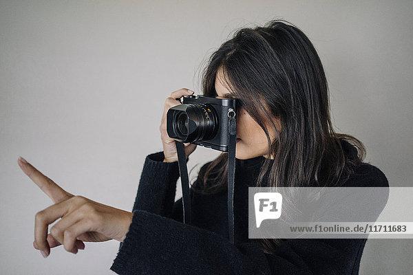 Dunkelhaarige junge Frau beim Fotografieren