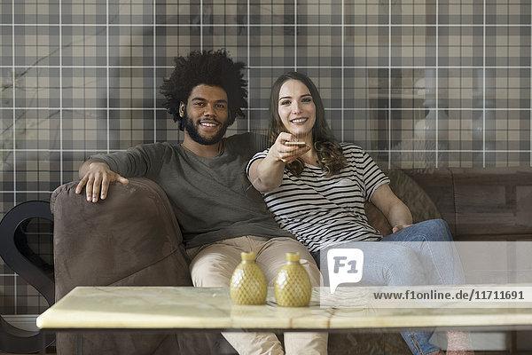 Lächelndes Paar sitzt auf der Couch und schaut fern.