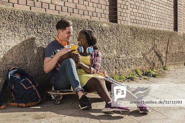 Junges Paar sitzt auf dem Boden  benutzt Smartphone