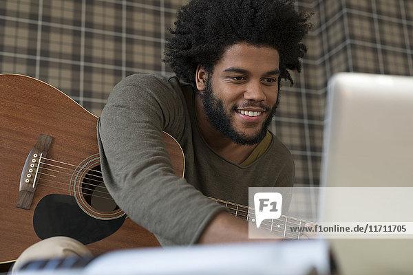 Mann mit Gitarre schaut auf Laptop