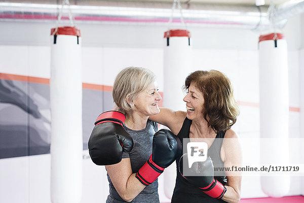 Zwei glückliche Seniorinnen mit Boxhandschuhen im Fitnessstudio