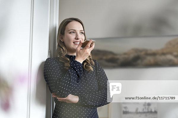 Lächelnde Frau zu Hause lehnt sich in den Türrahmen und spricht in das Smartphone.