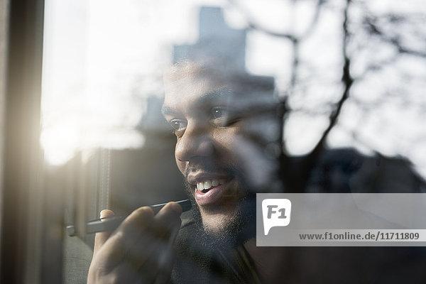 Mann am Fenster  der nach draußen schaut und ins Smartphone spricht