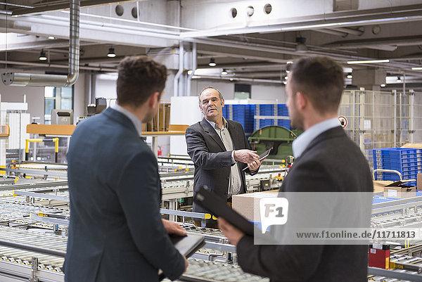 Drei Geschäftsleute am Förderband in der Fabrik