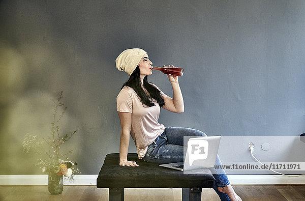 Junge Frau mit Laptop beim Trinken aus der Flasche