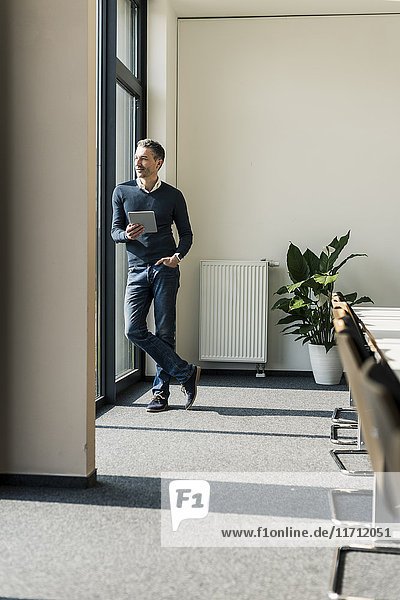 Geschäftsmann mit Tablette im Konferenzraum mit Blick durchs Fenster