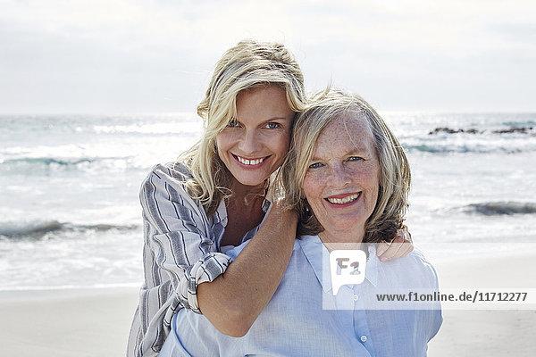 Mutter und Tochter umarmen sich am Meer.
