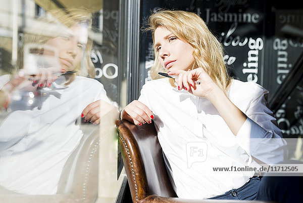 Geschäftsfrau in einem Café mit Blick aus dem Fenster