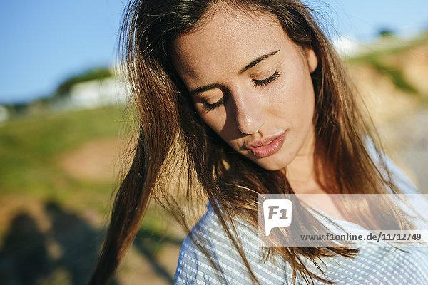 Porträt einer jungen Frau mit geschlossenen Augen bei Sonnenlicht