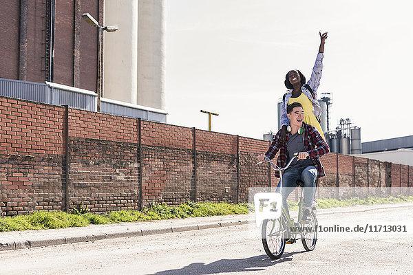 Junger Mann auf dem Fahrrad mit seiner Freundin auf dem Gestell stehend