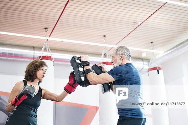 Fit Senior Frau Boxen mit ihrem Trainer