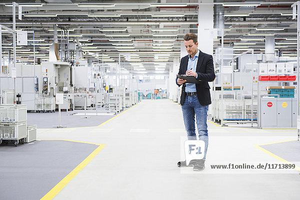 Mann  der in der Fabrikhalle steht und Notizen macht.