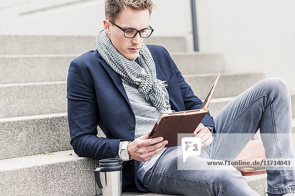 Young businessman sitting on stairs  using digital tablet