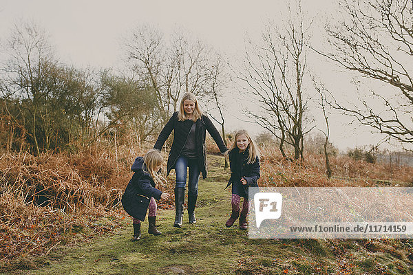 Mother and daughters running on a meadow together