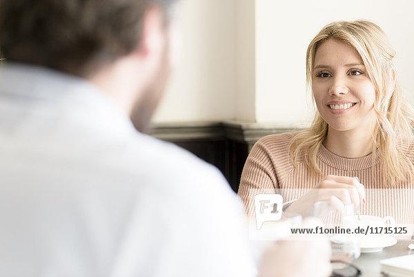 Lächelnde Frau schaut den Mann in einem Café an.