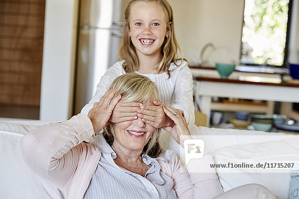 Kleines Mädchen  das Spaß mit seiner Großmutter zu Hause hat.