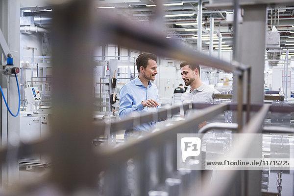 Zwei Männer  die in der Fabrikhalle reden.