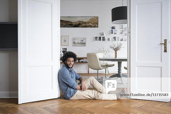 Mann zu Hause auf dem Boden sitzend auf Türrahmen im Wohnzimmer lehnend