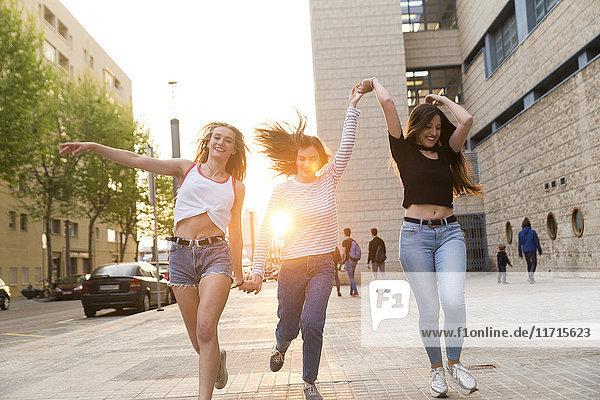 Drei glückliche junge Frauen laufen Hand in Hand auf dem Bürgersteig.
