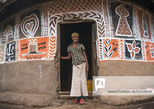 Ethiopian woman standing in front of her traditional painted house  Kembata  Alaba Kuito  Ethiopia.