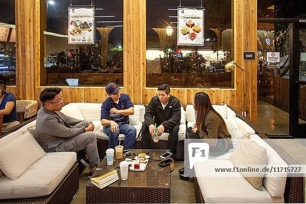 Four Asian American young adults relax on couches as they enjoy coffee and pastries at an European style cafe in Buena Park  CA. Note posters of food items.